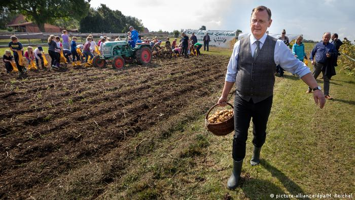 Ramelow carrying potatoes in field in Thuringia