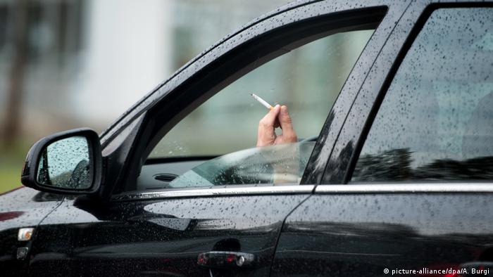 Mão de motorista segurando um cigarro para fora da janela do carro