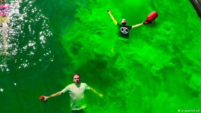 Extinction Rebellion protesters have colored a local river in Zurich acrid green and stage a die-in
