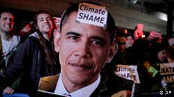 Activists holding a picture of Obama with Climate Shame written over it