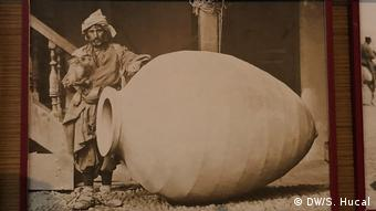 Georgian man in traditional dress stands alongside a qvevri, a clay pot used for making traditional Georgian wine