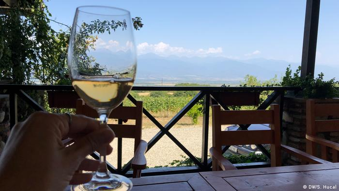 A glass of amber Georgian wine, a view of the vineyard in the background