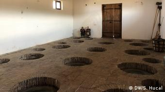 A storage room with holes in the ground for storing qvevri pots