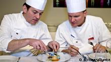 Zwei Jurymitglieder verkosten das Essen bei einem Kochwettbewerb | Verwendung weltweit, Keine Weitergabe an Wiederverkäufer.