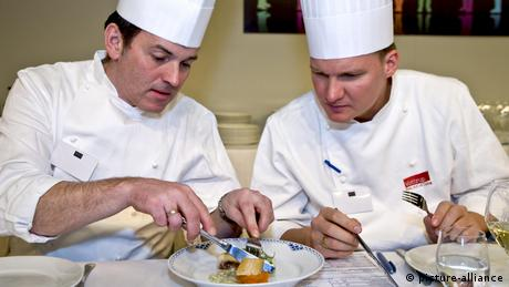 Two cooks testing food during a cooking competition