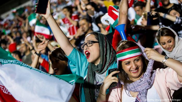 Iranian football supporters wave their national flags as they cheer for their national team during a screening of the Russia 2018 World Cup Group B football match between Iran and Spain in Azadi stadium in the capital Tehran on June 20, 2018