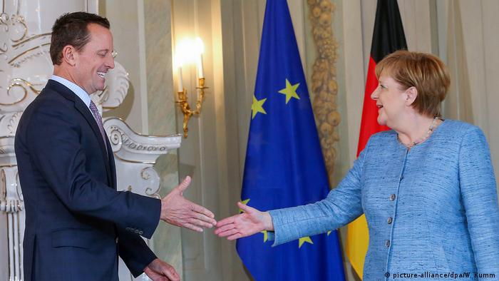 US Ambassador Richard Grenell approaches to shake hands with German Chancellor Angela Merkel