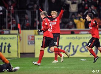 Mit zwei Toren sichert Kroos (l.) den Leverkusenern den Sieg. Er feiert mit Kiessling und Barnetta. (Foto: AP)