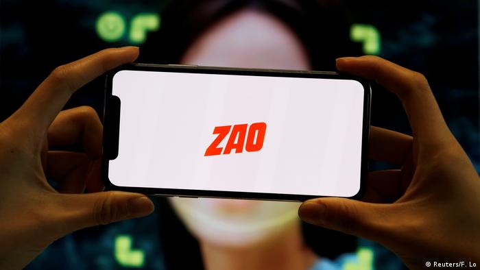 The logo of the Chinese app ZAO is seen on a mobile phone screen in front of an advertisement of the app