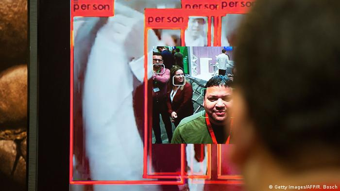 A man stands in front of face-recognition system at an expo in South Africa