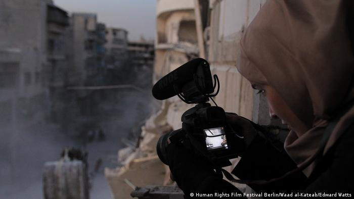 A still from 'For Sama' shows a woman photographhing out a window of a destroyed building (Human Rights Film Festival Berlin/Waad al-Kateab/Edward Watts)