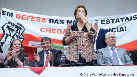 Dilma, em pé, segura um microfone e manda beijo para o público. Ao fundo, uma grande faixa contra a privatização de estatais.