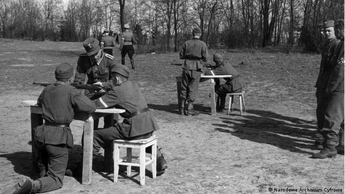 Młodzież z Hitlerjugend podczas ćwiczeń w posługiwaniu się bronią na obozie w Kobierzynie. Zdjęcie zrobione po wymordowaniu pacjentów szpitala 23 czerwca 1942 roku.