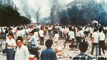 ARCHIV - Rauchsäulen, Verwüstung und ratlose Menschen auf der Changan Avenue in Peking (Archivfoto vom 04.06.1989) Militär hatte auf dem Platz des Himmlischen Friedens (Tien?anmen) in Peking, auf dem Studenten für mehr Demokratie, Pressefreiheit und gegen Parteiprivilegien demonstrierten, ein Blutbad angerichtet. Die Proteste hatten mit dem Tod des in Ungnade gefallenen Chefs der Kommunistischen Partei Chinas, Hu Yaobang, am 15. April 1989 begonnen. Studenten strömten zum Platz des Himmlischen Friedens um Kränze niederzulegen. Die Trauer verwandelte sich in eine Bewegung, die Millionen von Chinesen gegen Korruption und für Demokratie mobilisierte. Am 4. Juni 1989 wurden die Proteste durch den Einsatz von Militär blutig beendet. Die genaue Zahl der Opfer bleibt unbekannt. Foto: Kyodo News (zu Themenpaket Tian'anmen vom 01.06.2009) +++(c) dpa - Bildfunk+++ |