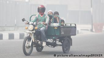 People cover their heads and faces to protect themselves from bad air in Pangkalanbun, Central Kalimantan