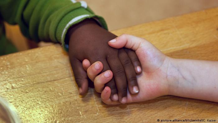 Mãos de duas crianças, durante aperto de mãos, uma negra, outra branca