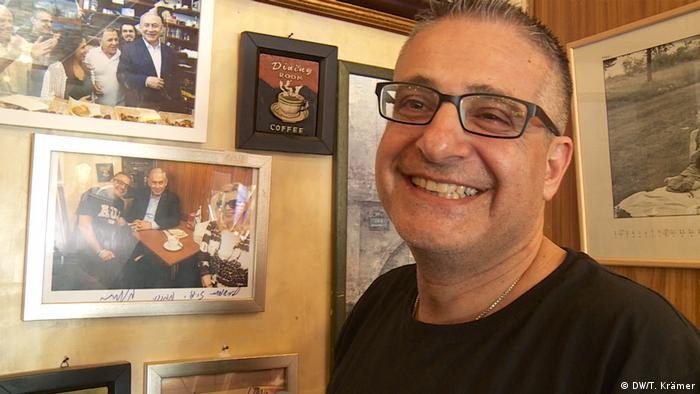 A cafe owner in front of pictures on the walls