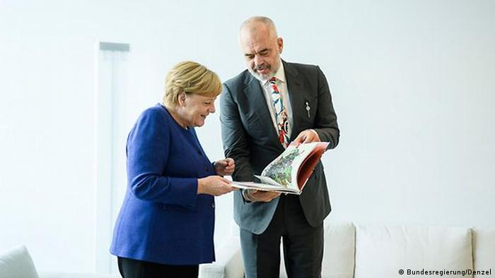 Kancelarja gjermane Angele Merkel duke soditur albumin me piktura të Edi Ramës, në vitin 20219 në Berlin, pak përpara se Shqipëria të merrte dritën jeshile nga Bundestagu për çeljen e negociatave