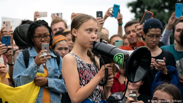 Teenage Swedish climate activist Greta Thunberg delivers brief remarks surrounded by other student environmental advocates in Washington.