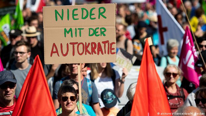 A protester holds a sign which states down with Auto-cracy (picture-alliance/dpa/M. Becker)