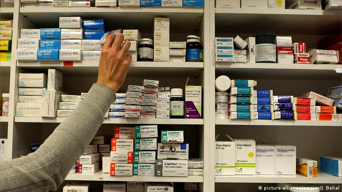A hand holding a box from shelves of medicine (picture-alliance/empics/J. Behal)