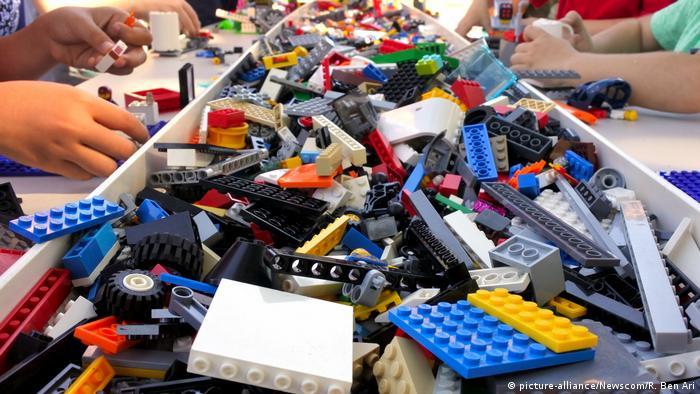 Peças de Lego numa mesa e algumas mãos de crianças