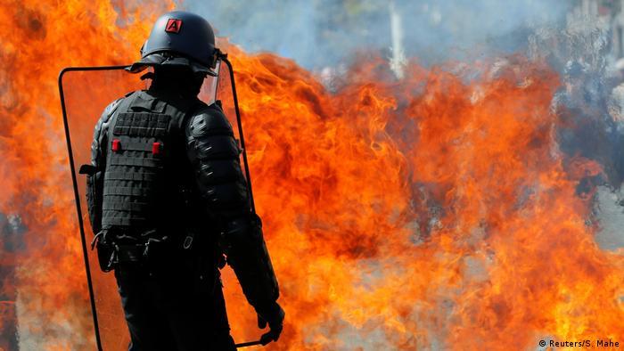 Пламя от бутылки с зажигательной смесью и полицейский со щитом