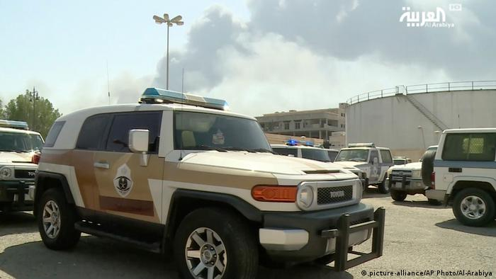 A Saudi police cruiser sits in a parking lot as smoke rises from a fire at the Abqaiq oil processing facility