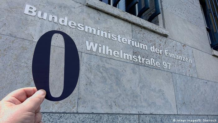 Someone holds up a black zero outside the German Ministry of Finance.