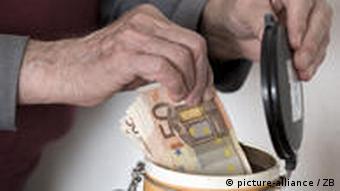Stariji ruka stavlja novac u kuhinjksu posudu