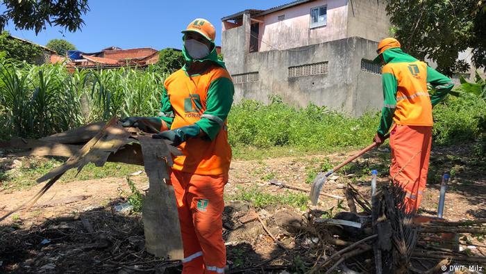 Na luta contra a dengue, funcionários limpam terreno baldio em Aracaju, Sergipe