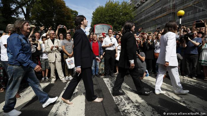 A crowd of people crossing the street like the Beatles themselves did