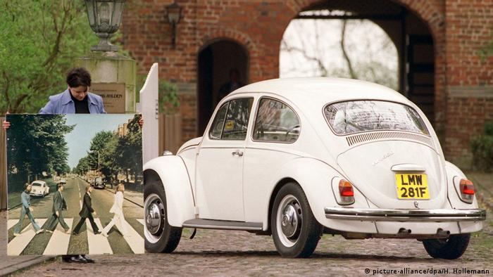 White VW Beetle and next to it, the picture of the Beatles crossing the street
