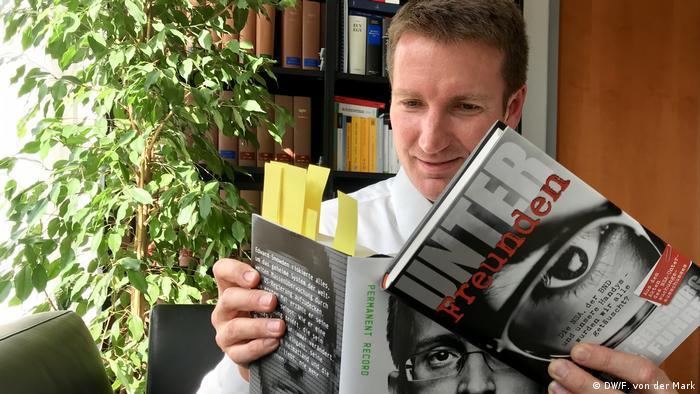 Patrick Sensburg holding his book and reading Edward Snowden's (DW/F. von der Mark)