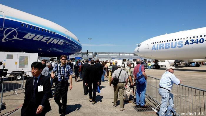 Gente mirando aviones de Boeing y Airbus.