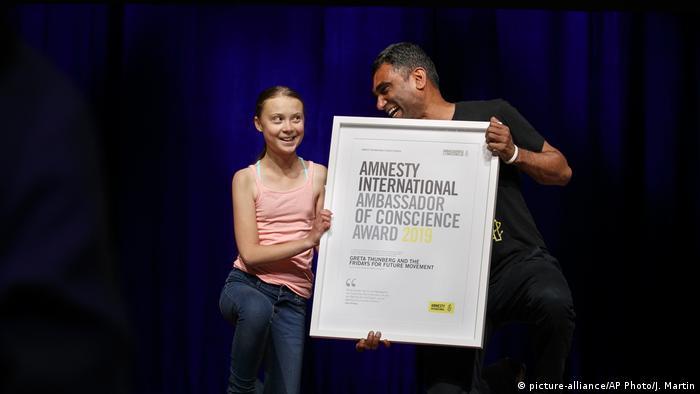 GretaThunberg recebe o prêmio das mãos do secretário-geral da Anistia Internacional, Kumi Naidoo