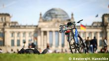 People lie on a meadow in front of the Reichstag building during a sunny day in Berlin, Germany, September 15, 2019. REUTERS/Hannibal Hanschke