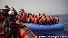 Rescued migrants in rubber dinghy (picture-alliance/AP/R. Brito)