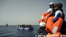 SOS Mediterranee rescuers hold life jackets as migrants on an overcrowded wooden boat wait to be saved some 53 nautical miles (98 kilometers) from the coast of Libya in the Mediterranean Sea, Tuesday, Sept. 17, 2019. The humanitarian rescue ship Ocean Viking pulled 48 people from the small boat including a newborn and a pregnant woman. (AP Photo/Renata Brito)  