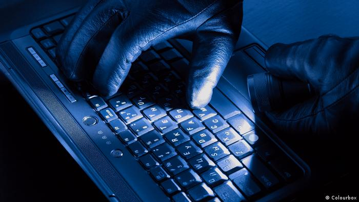 Gloved hands of hacker on a keyboard