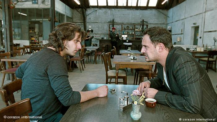 Two men seated at a table in a restaurant in 'Soul Kitchen' (corazon international)
