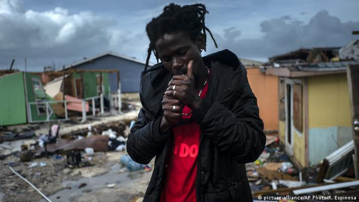 Man lights a cigarette next to the rubble of his home after Hurricane Dorian struck the Bahamas