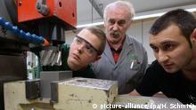 Zwei junge Männer vor einer mschine, ein älterer schaut ihnen über die Schulter (picture-alliance/dpa/H. Schmidt)