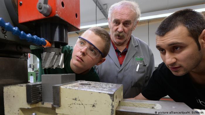Zwei junge Menschen und ein älterer Mann blicken in einer Werkstatt auf eine Maschine (picture-alliance/dpa/H. Schmidt)