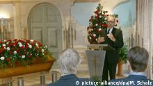 Ein Trauerredner steht an einem Rednerpult in einem Bestattungsinstitut. Links neben ihm steht ein blumenbedeckter Sarg. (picture-alliance/dpa/M. Scholz)