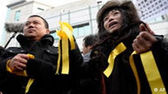 Supporters of Chinese dissident Liu Xiaobo wear yellow ribbons to show their solidarity outside the No. 1 Intermediate People's Court where Liu's trial is taking place in Beijing