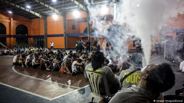 Police personnel smoke using e-cigarette while guarding the holding area