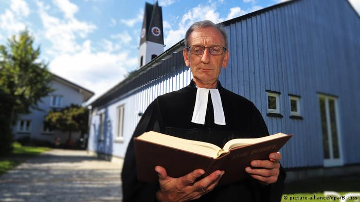 Protestant Pastor Ulrich Gampert reading from a bible standing outside a wooden church