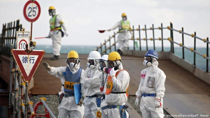 Workers wearing protective suits and masks stand near the No. 3 and No.4 reactor buildings at Tokyo Electric Power Co's (TEPCO) tsunami-crippled Fukushima Daiichi nuclear power plant in Okuma town