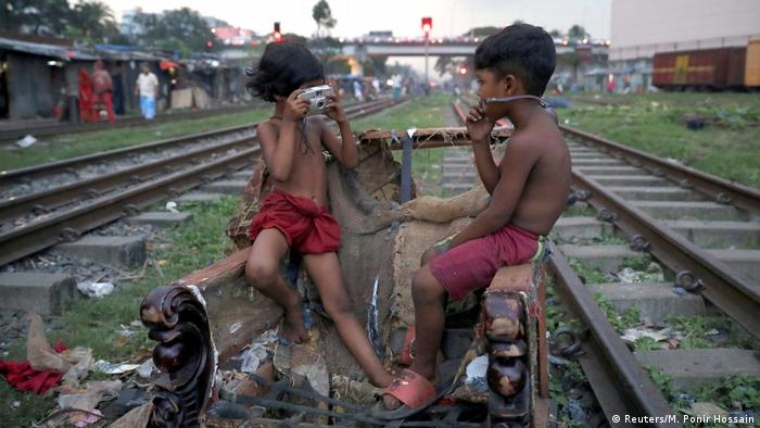 Djeca se igraju izmežu šina i smeća u Daki, Bangladeš